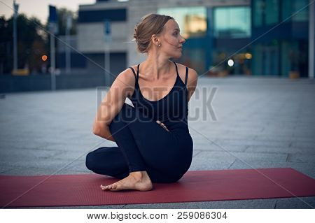 Beautiful Young Woman Practices Yoga Asana Marichiasana 4 - Sage Pose Outdoors Against The Backgroun