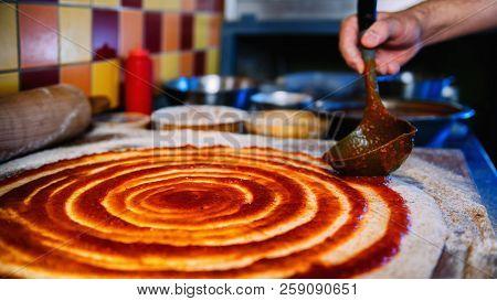 Chef Spreading Tomato Sauce On Pizza Dough