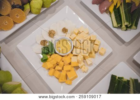Cheese Snack Cubes Stand On A Table In A Square Plate Along With Other Dishes