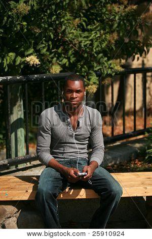 ein Afroamerikaner modellieren männlich hört Musik auf seine persönliche mp3-Musik-player