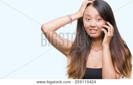 Young asian woman speaking on the phone over isolated background stressed with hand on head, shocked with shame and surprise face, angry and frustrated. Fear and upset for mistake.