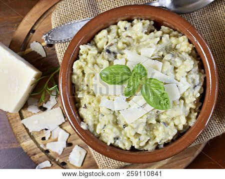 Delicious Risotto Dish In A Brown Bowl, With Mushrooms And Parmesan Cheese. Risotto A La Milanese, C