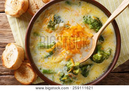 Broccoli Cheese Soup Served With Toasted Bread Close-up In A Bowl. Horizontal Top View