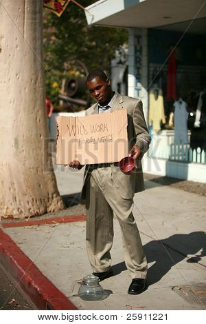 a thursty male model stands on a city street with a cardboard sign that reads