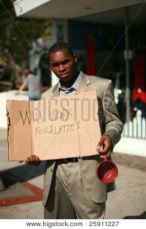 a thursty american male model stands on a city street with a cardboard sign that reads