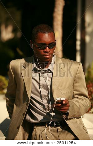a well dressed Male Model listens to his personal digital music player