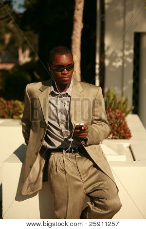 a well dressed african american Male Model listens to his personal digital music player