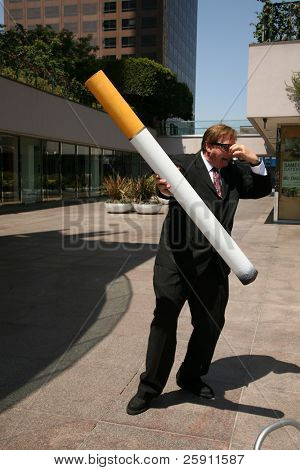Anti-Smoking Concepts. A business man in a suit holds a Giant Cigarette,  with a book of matches