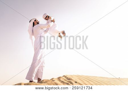 Arabian Man And Son Playing In The Desert