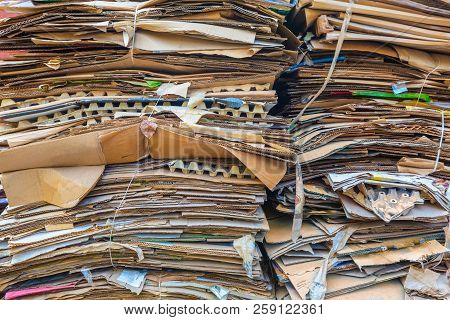 Stack Of Cartons And Paper Waiting To Be Picked Up By The Garbage Trucks. Concept Of Recycling Of Wa