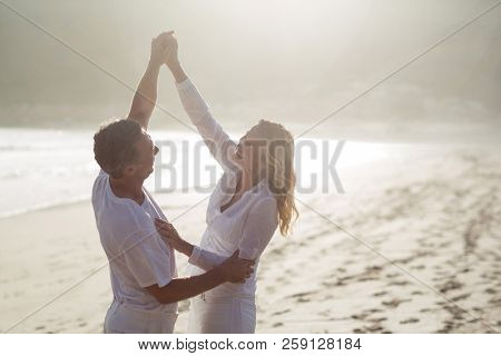 Happy mature couple having fun together at beach