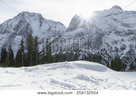 Amazing Winter Landscape With The Rocky Austrian Alps Mountains, A Fir Forest, And Piles Of Snow, On