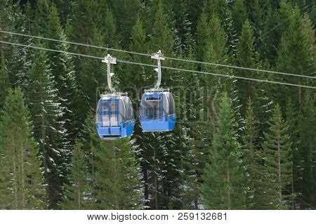 Two Cable Cars, That Go In Opposite Ways, Meet Over The Snowy Evergreen Fir Forest, In The Alps Moun