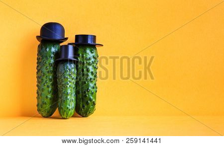 Comical Green Cucumbers Family On Yellow Background. Three Funny Vegetables With Black Old Fashioned