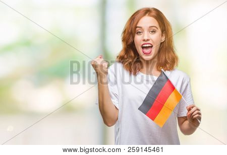Young beautiful woman holding flag of germany over isolated background screaming proud and celebrating victory and success very excited, cheering emotion