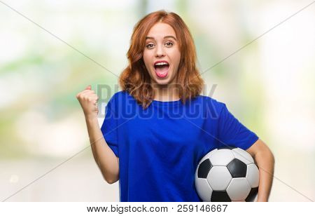 Young beautiful woman over isolated background holding soccer football ball screaming proud and celebrating victory and success very excited, cheering emotion