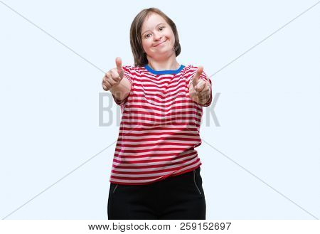 Young adult woman with down syndrome over isolated background approving doing positive gesture with hand, thumbs up smiling and happy for success. Looking at the camera, winner gesture.