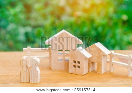 The Family Stands Near Their Home. Concept Of Real Estate. Buying, Selling, Renting A House. Propert