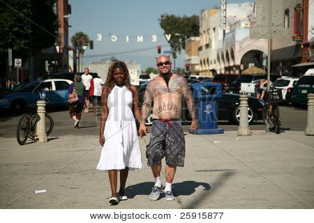 a unique couple walk hand in hand on a hot summer day in