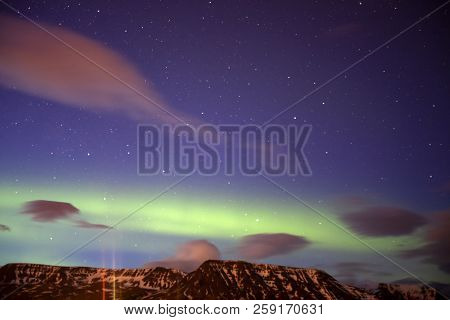 A Light Show Above The Mountains In Iceland