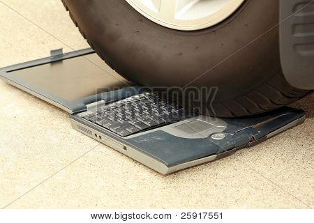 laptop computer driven over by a car, represents computer damage, loss of data, emergency and more