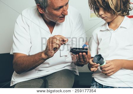 The Pediatric Endocrine Doctor Explaining To A Young Diabetic Patient The Insulin Pump Functions In