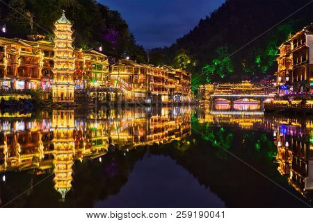 Chinese tourist attraction destination - Feng Huang Ancient Town (Phoenix Ancient Town) on Tuo Jiang River illuminated at night. Hunan Province, China