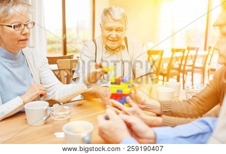 Seniors with dementia and Alzheimer's play together with building blocks in the nursing home