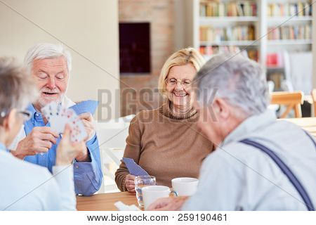Senior retired friends play cards in their spare time or at retirement home