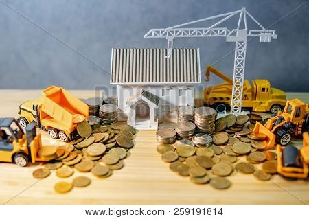House, Crane And Construction Truck Models With Gold Coins Spilling On Wooden Table. Real Estate Dev