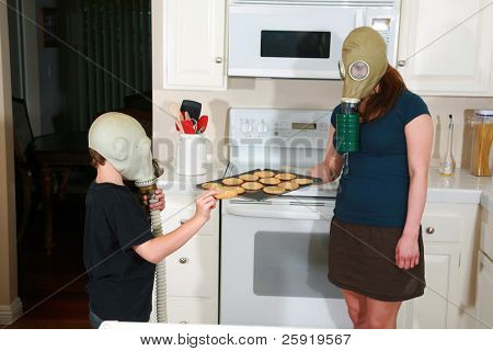 mother and son enjoy hot fresh baked cookies in their kitchen while wearing gas masks in the Future when Global Warming and CO2 have destroyed our way of living