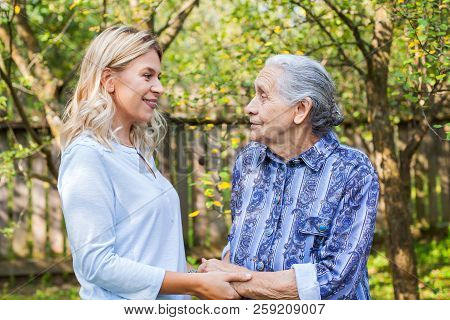 Friendly Caregiver Walking With Old Lady In The Garden - Medical Care