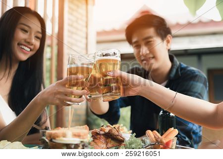 Group Of Asian People Cheering Beer At Restaurant Happy Hour In Restaurant.