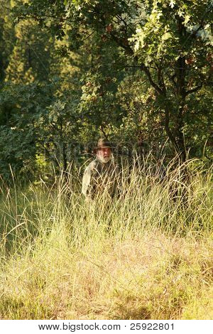a hunter hides in the woods looking to find and shoot a Sasquatch Monster