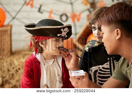 Little Boy In Pirate Costume Having His Face Painted For Halloween
