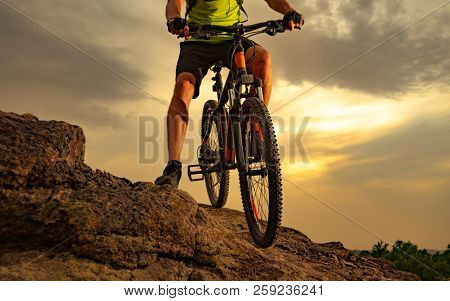 Enduro Cyclist Riding the Mountain Bike on the Rocky Trail at Sunset. Close-up of Bicycle. Active Lifestyle Concept.