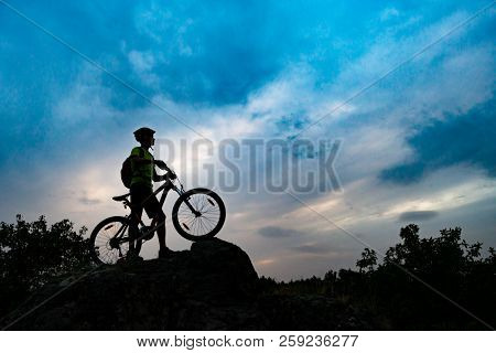 Silhouette of Cyclist with Mountain Bike on the Rock at Sunset. Extreme Sports and Enduro Cycling Concept.