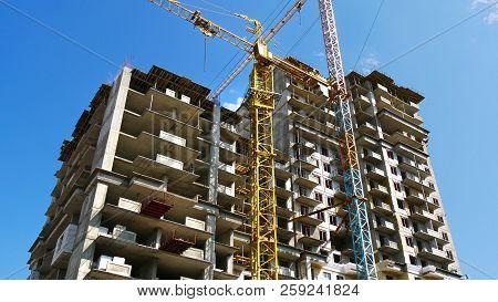 Skyscraper Construction. Two Cranes Near Building Under Construction. Construction Site.