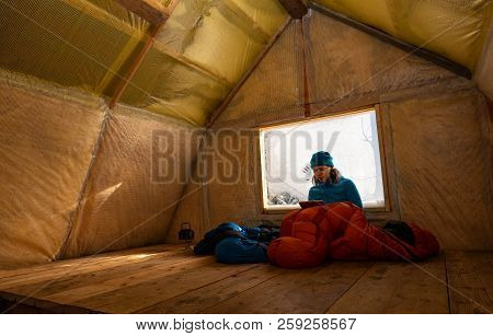 Traveler, Woman Rests In The Old Mountain Hut, Sits In A Sleeping Bag Next To A Window Covered With