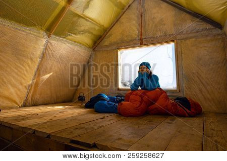 Happy Traveler, Woman Relaxes In The Old Mountain Hut, Sits In A Sleeping Bag Next To A Window Cover