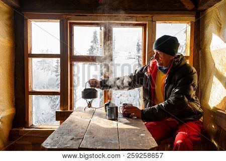 Adventurer Is Drinking Coffee And Dreaming In A Old Mountain Hut. Awesome Winter Travel In Wildernes
