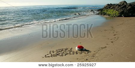"""the words """"Merry Christmas"""" written in wet sand with a """"Santa Hat"""" on a secluded beach in """"southern california"""" with the tide of the pacific ocean and blue sky in the background"""
