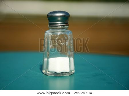 a salt shake half filled with iodized table salt on an table outside with low depth of field poster