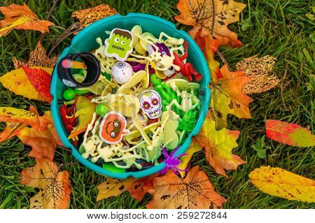 Halloween teal basket with party favors for kids with food allergy. trick-or-treating. Teal pumpkin. the concept of health for children in the Halloween season poster