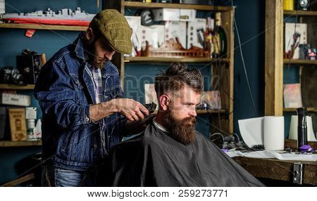 Hipster Client Getting Haircut. Barber With Hair Clipper Works On Haircut Of Bearded Guy, Retro Barb