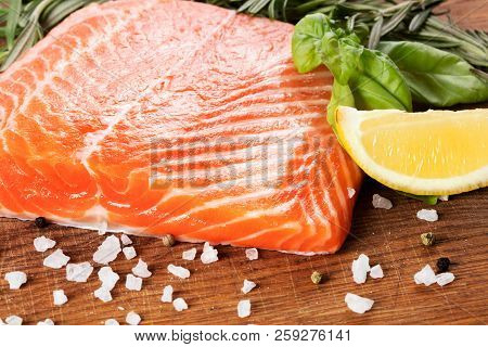 Big Slice Of Raw Salmon With Herbs On Wooden Background