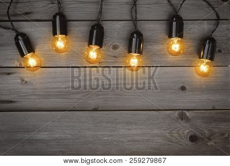 Holiday Glowing Garland Of Light Bulbs On Vintage Wooden Background