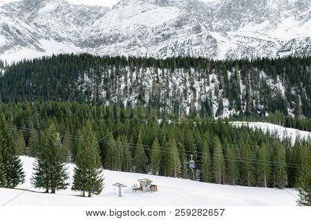 Curved Foothills And The Rocky Alps Mountains Covered By Snow And Green Fir Trees, A Cableway System