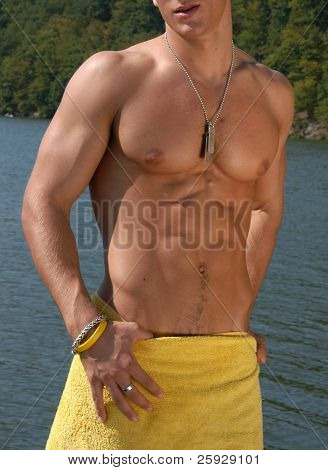 Muscular male torso with army tags wrapped a towel
