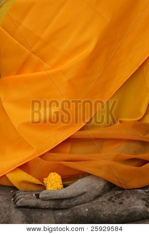 Stone statue of Buddha wrapped in orange fabric in Nakhon Pathom, Thailand